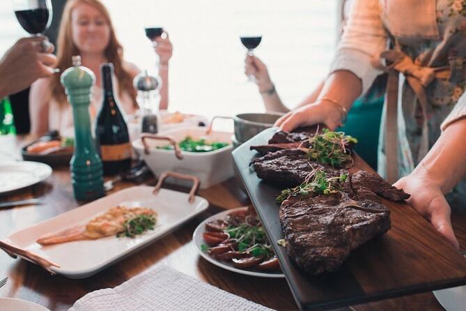 personnes à table autour d'un plant de viande