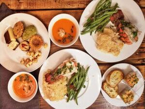 repas de st-valentin pour 2 personnes, repas de 4 services avec 2 queues de homard avec la sauce, accompagnés d'asperges sautées et 2 potages aux légumes et 2 verrines de tartare de saumon
